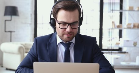 Male executive wears headset video calling on laptop. Businessman webinar speaker streaming live web training. Call center agent, service support manager speaking to distance customer in webcam chat.