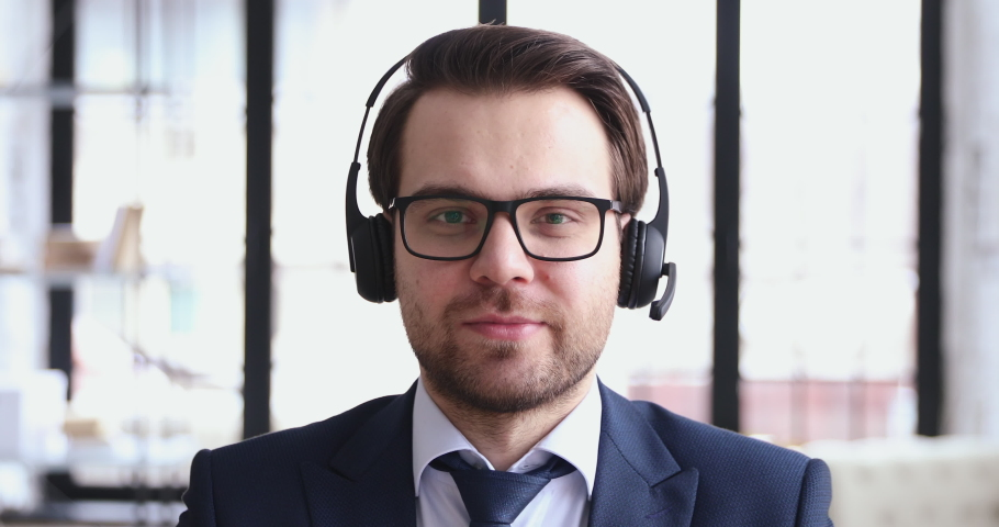 Friendly telemarketer operator representative speaking to web camera. Businessman wears headset suit video conference calling. Customer support service assistant on call center phone talk. Webcam view Royalty-Free Stock Footage #1048284724