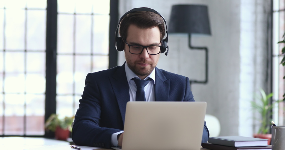 Confident businessman wears suit and headset makes conference video call on laptop. Male call center agent, customer support manager or telemarketer communicating in webcam chat on computer in office.