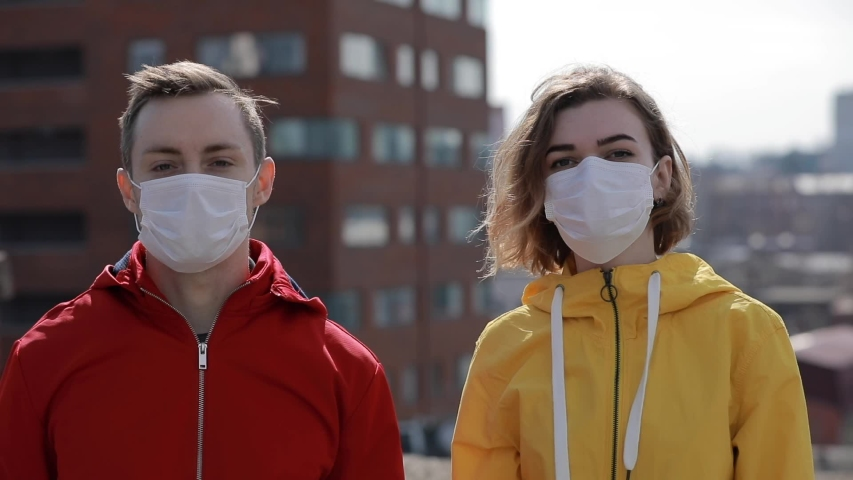 Virus epidemic is finish in a city, man and woman take off surgical masks from their faces | Shutterstock HD Video #1048310671