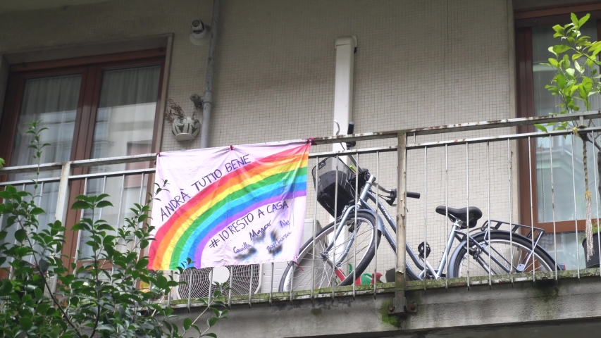 """Europe, Italy, Milan March 2020, Coronavirus emergency - On the windows of the city balcony hang sheets designed by children with rainbow and the words """"everything will be fine"""" ( Tutto Andra' bene )"""