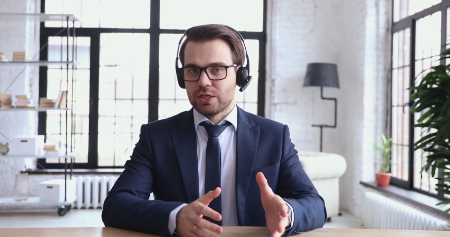 Confident male support service representative wears suit and tie talking to web camera. Businessman in headset communicates by conference video call. Helpline manager speaking to customer, webcam view