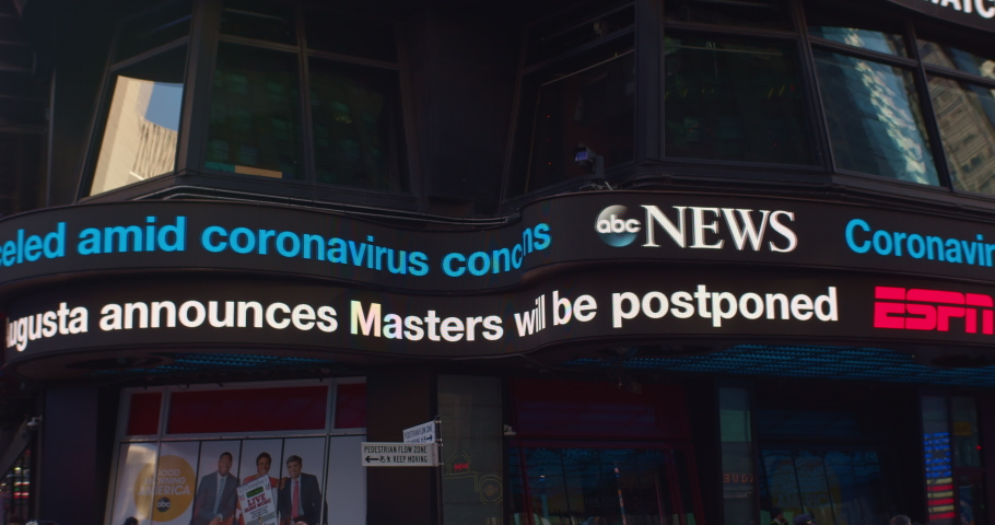 New York, New York / United States - March 13 2020: ABC News ticker displays latest headlines related to the Coronavirus, COVID-19. Effect on democratic primary. Postponement of Masters Golf Event.