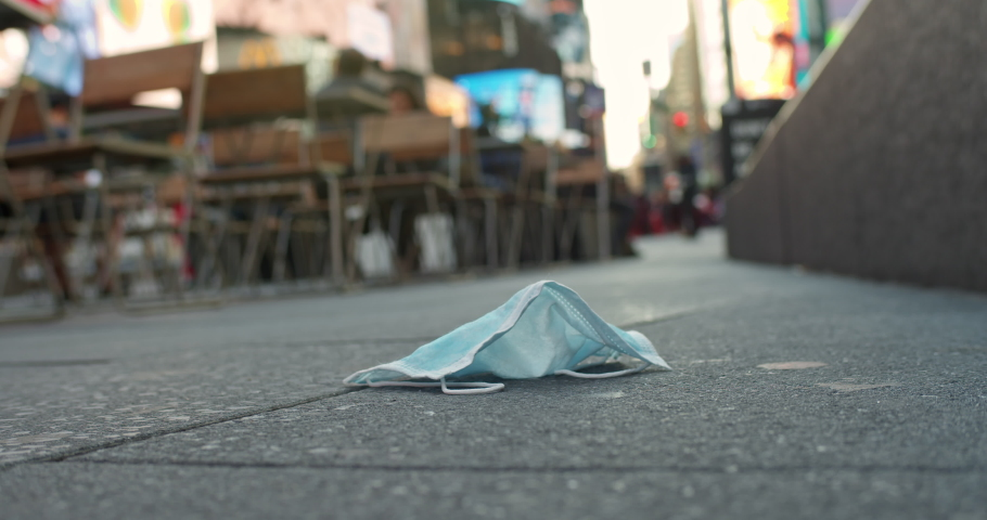 Discarded surgical mask lay on the ground in New York's Times Square. Broadway's theater district shutdown do to Coronavirus, COVID-19 Royalty-Free Stock Footage #1048334281