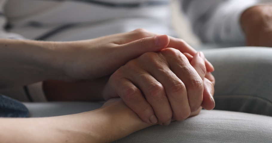 Close up young woman stroking hand of middle aged mother, enjoying sweet tender moment. Millennial caregiver or grown up daughter showing support respect to elderly mom, helping in health care. Royalty-Free Stock Footage #1048334791