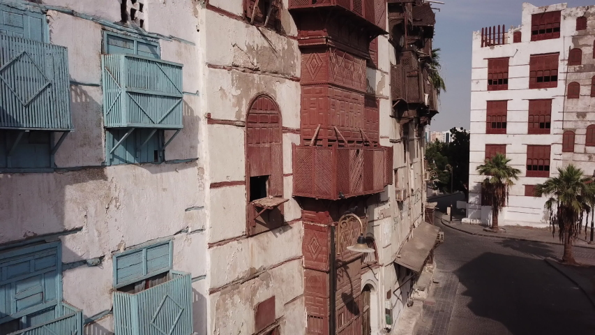 Drone flight past historic merchant houses made of coral stones and carved wood in Jeddah (two pigeons fly away in the shot)  | Shutterstock HD Video #1048355032