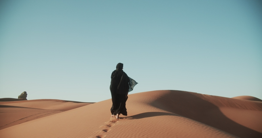 Young beautiful girl in traditional Abaya dress walks barefoot through the dunes in the desert of Dubai. 4K Slow Motion Royalty-Free Stock Footage #1048362667
