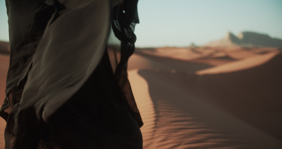 Close-up of girl in traditional Abaya dress walking barefoot along the dunes in the desert of Dubai. 4K Slow Motion #1048362712