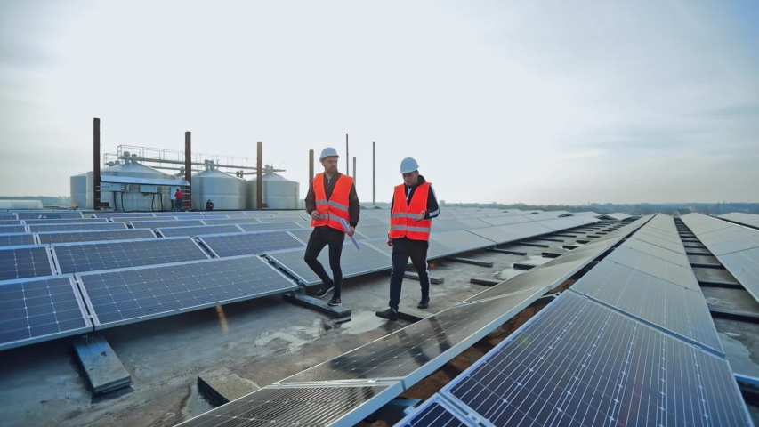 New solar farm under the blue sky. Workers in special outfit walk and talk about sunny cells installation. Modern solar panels produce clean electricity.