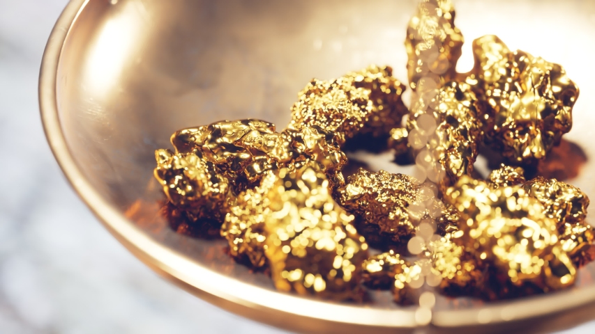 Close up of a jewelry scale dish with gold nuggets. Weighting gold ores on an old brass scale dish for trade or exchange. Concept of Wealth, treasure, fortune, success, luxury, money    Shutterstock HD Video #1048369615