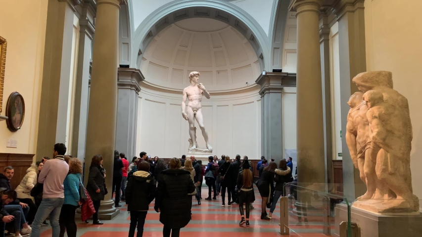 Florence, Italy -  January 25, 2020: People inside of famous Florence Accademia art museum gallery looking at view of David statue of Michelangelo