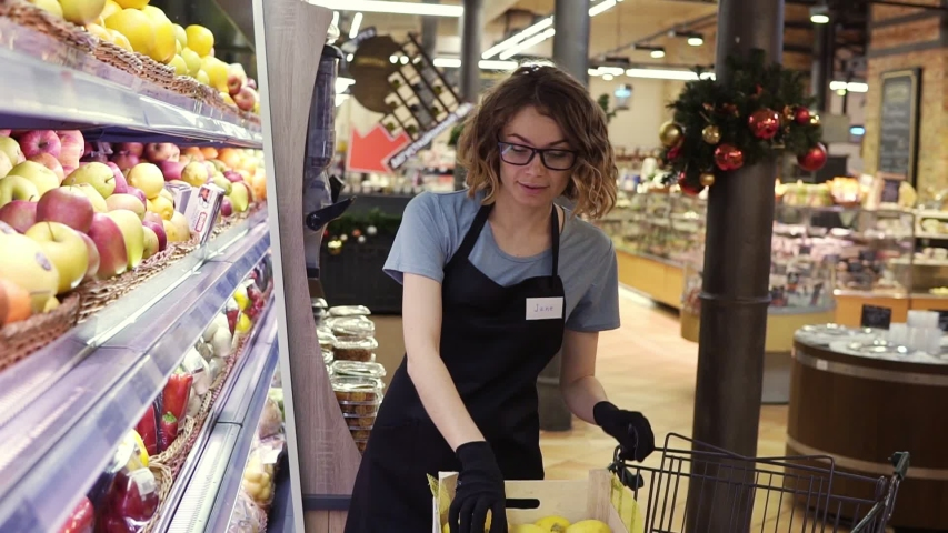 Side view of pretty caucasian worker in black apron and gloves stocking the fruits in supermarket. Young employee at work. Curly female arranging fruits on shelf