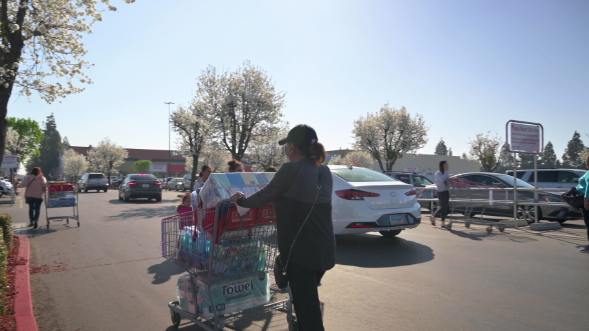 March 13, 2020: Woman wearing mask pushes shopping cart with toilet paper and other goods in Costco parking lot. Long line of people behind here trying to enter the store.