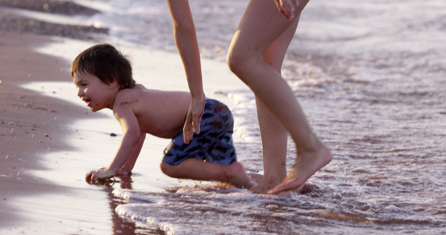 Toddler boy crawling on ocean beach stands up with mother - side profile