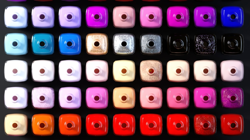 Seamless looping animation with many opened nail polish bottles arranged by shade. Top view of vibrant, beautiful, timeless fashion colors. Elegant glass bottles on the dark surface.