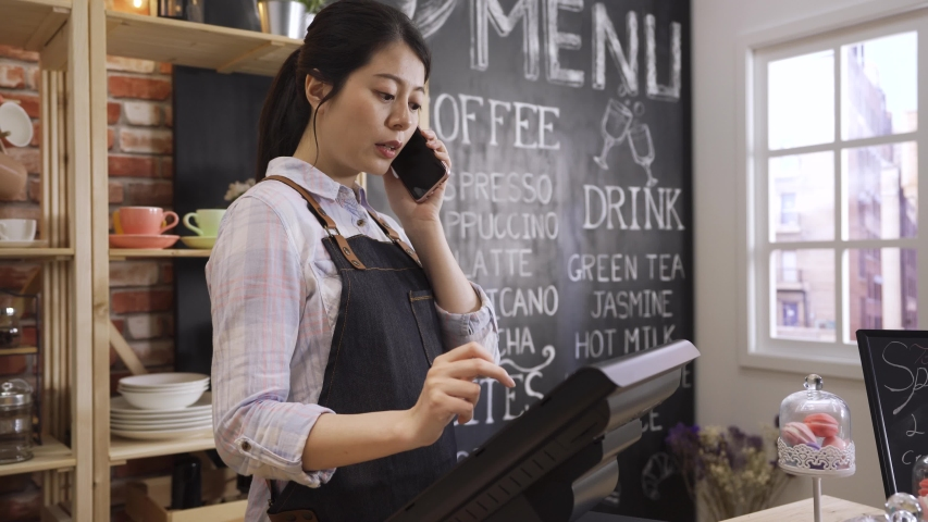 Asian barista talking on mobile phone in coffee shop. Cafe restaurant service small business owner food and drink industry concept. girl bartender taking order with customer on cellphone using tablet Royalty-Free Stock Footage #1048390648
