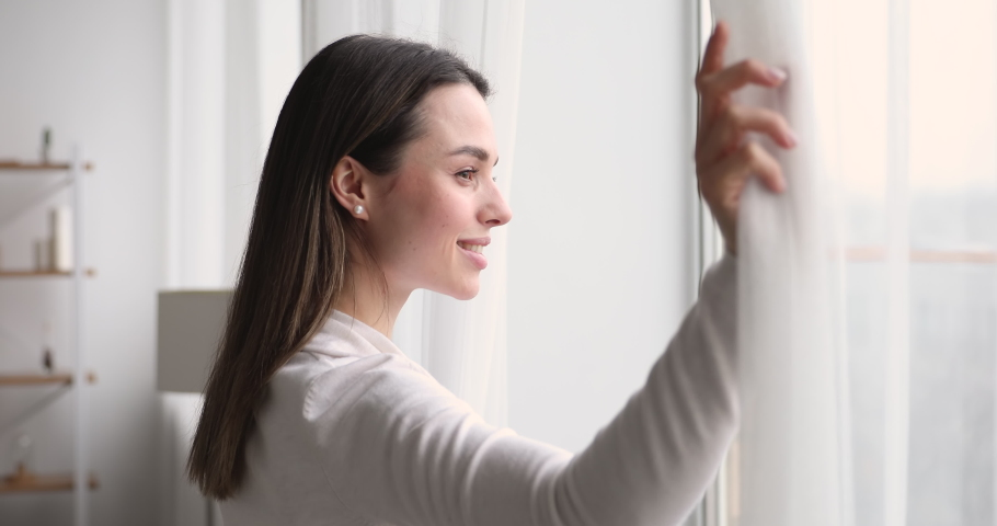 Young woman opening curtain looking through window. Happy confident lady enjoying beautiful view and dreaming at home. Smiling girl contemplating feeling hope peaceful morning standing in apartment