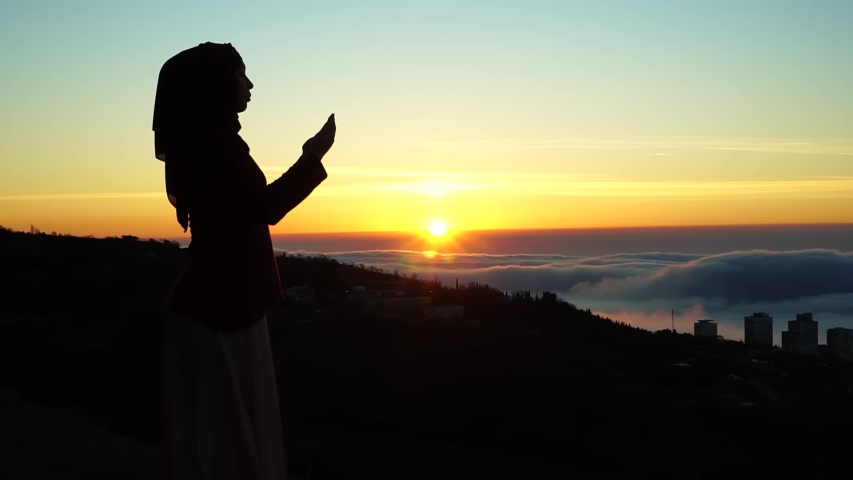 Muslim woman in a hijab are praying. The Holy month of Ramadan. Morning prayer and the beginning of fasting. Silhouette at sunrise