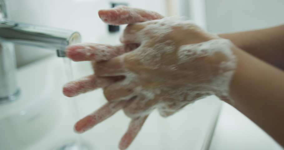 Coronavirus pandemic prevention wash hands with soap warm water rubbing fingers washing frequently or using hand sanitizer gel. | Shutterstock HD Video #1048399522