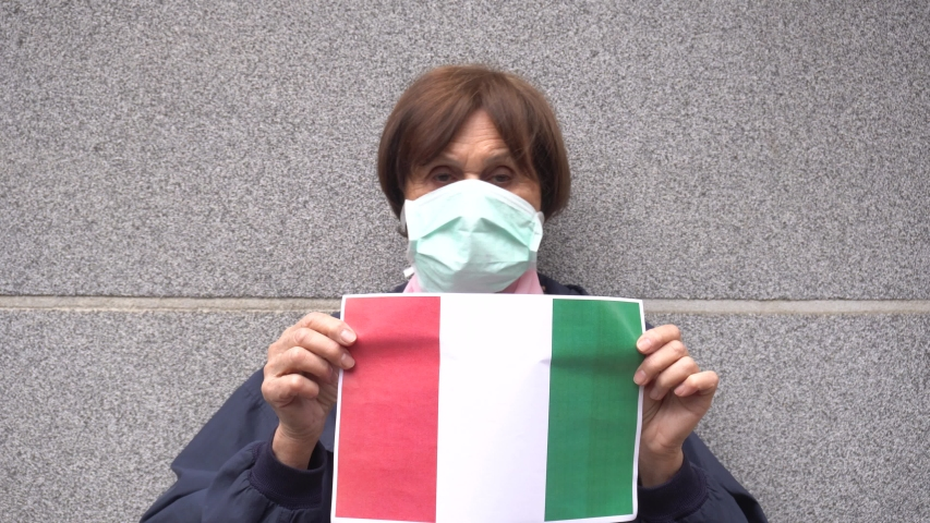 Europe - Italy - Milan - 70 year old lady with  mask on face to protect herself from the global epidemic of Novel Coronavirus n-cov 19 shows the flags of Italy infected - italian lockdown quarantine  Royalty-Free Stock Footage #1048403188