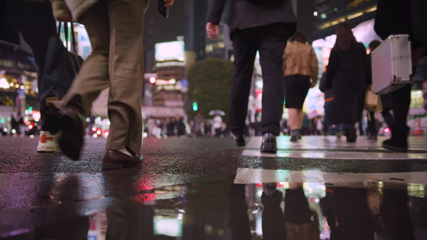 Low angle shots of people crossing Shibuya square on a rainy night. Showing shoppers and night life in the neon city. Tokyo, Japan.