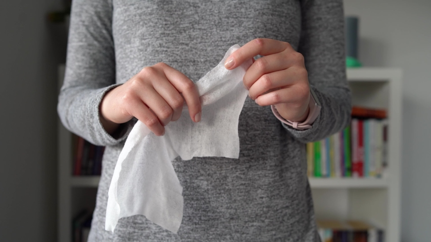 Close up on midsection of young caucasian woman hands wiping using white alcohol tissue cleaning disinfection from virus and bacteria in day at home or office front view  | Shutterstock HD Video #1048416481
