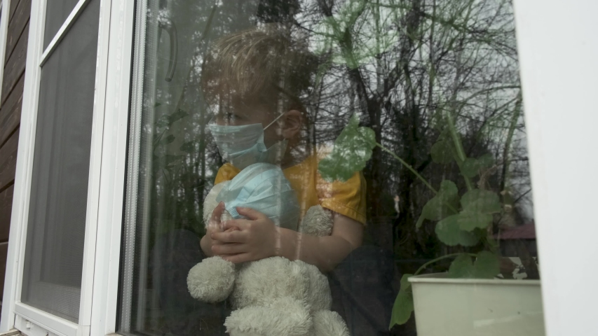 Stay at home quarantine for coronavirus pandemic prevention. Child and his teddy bear both in protective medical masks sits on windowsill and looks out window. View from street. Prevention epidemic Royalty-Free Stock Footage #1048417516
