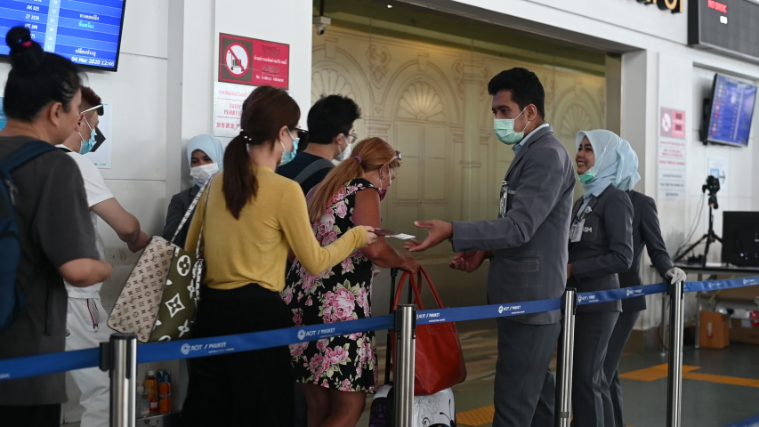 Phuket, Thailand - March 04 2020: Passengers and airport staff wearing face masks at security control. Getting temperature checked for CoronaVirus before the flight.