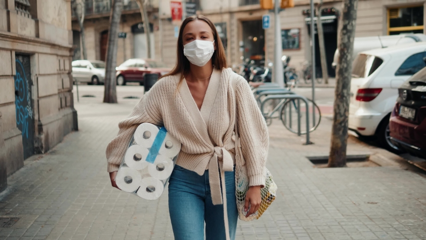 Woman walking in medical mask with toilet paper and packs of pasta food shopping bags during the quarantine coronavirus COVID-19 pandemic in 2019-2020 coronavirus quarantine