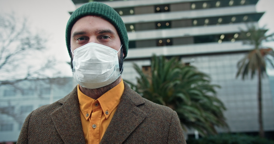 Young student hipster wearing protective coronavirus medical mask on city street, skyscraper on background.Concept of health and safety life, N1H1 coronavirus, virus protection, pandemic in world | Shutterstock HD Video #1048422934