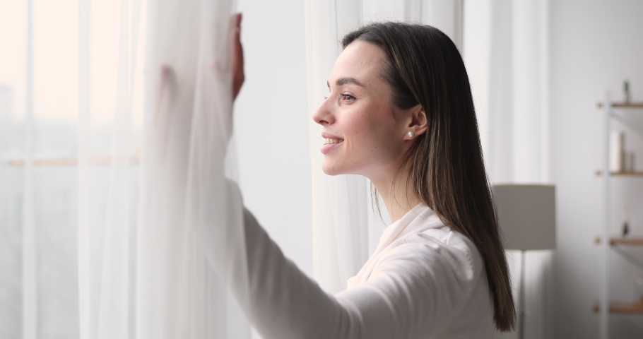 Happy young woman opens window lace looking outside apartment. Smiling mindful attractive lady watching beautiful cityscape view enjoying dreaming and contemplating feeling hope concept. Side view | Shutterstock HD Video #1048429234