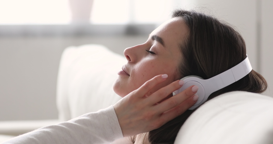 Serene young woman relaxing on comfortable sofa with eyes closed wearing headphones. Pretty lady enjoys listening chill music audio sound meditating feeling no stress at home. Close up side view | Shutterstock HD Video #1048429252