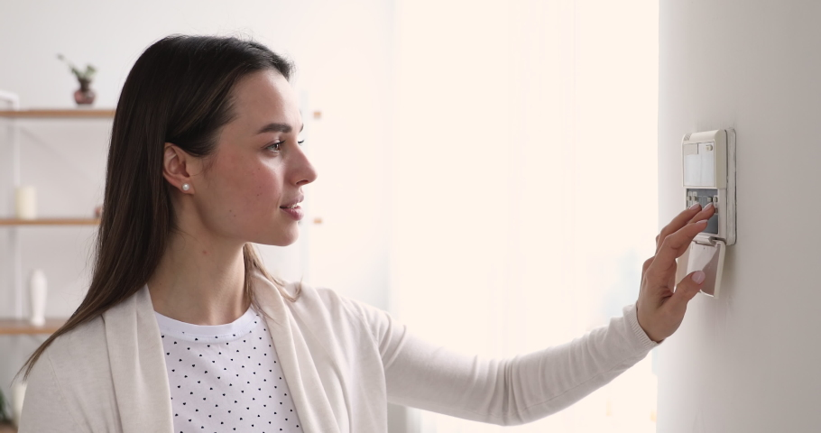 Young woman setting smart home security system concept. Smiling lady pressing buttons using automated house safety, heating and electricity control easy secure technology in modern apartment. Royalty-Free Stock Footage #1048429270
