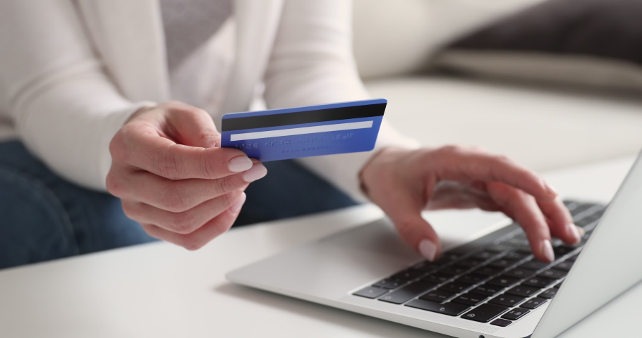 Female customer holding credit card paying online on laptop. Woman buying making secure digital electronic payment on website. Internet shopping with ebanking ecommerce service concept. Close up view Royalty-Free Stock Footage #1048429303