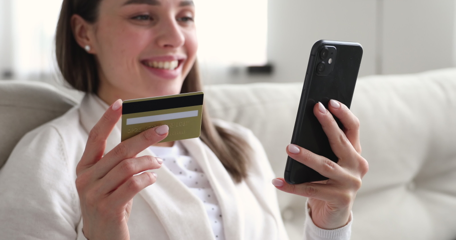 Female customer paying with credit card on smartphone. Happy woman consumer using e-bank app on phone making online purchase ecommerce money transaction, secure mobile payment concept. Close up view Royalty-Free Stock Footage #1048429306