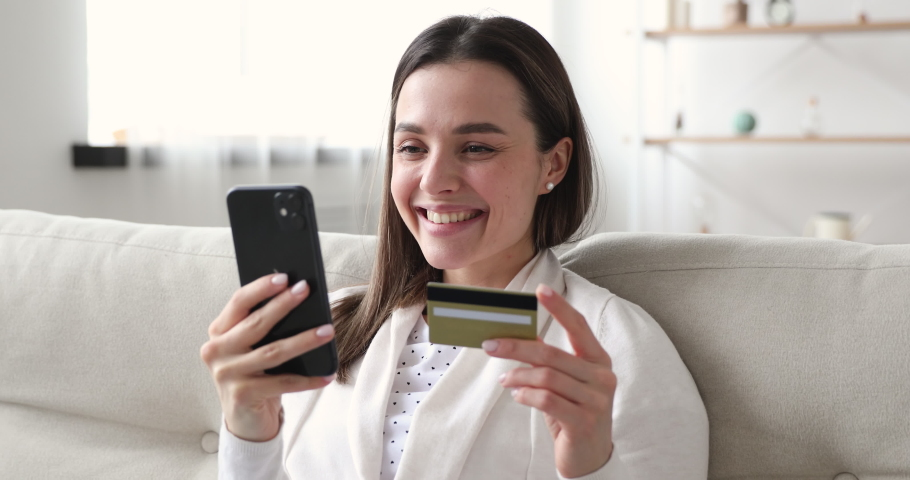 Smiling young woman consumer shopping online on smartphone ordering purchase. Happy female customer shopper holding cell phone and credit card making easy mobile payment in e-banking app concept. Royalty-Free Stock Footage #1048429309