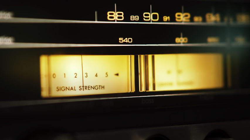 """Analog dial VU signal indicators on a vintage stereo receiver. Needle is moving and words """"Signal Strength"""" are printed on a yellow faceplate. 