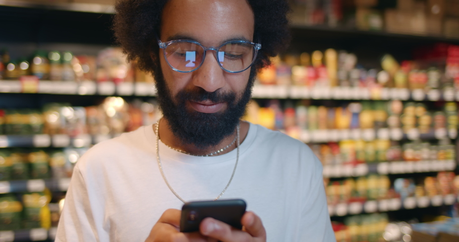 Close up of man using his smartphone while standing in food store. Bearded guy in glasses texting with wife on mobilephone while doing shopping in supermarket. Blurred background. | Shutterstock HD Video #1048434679