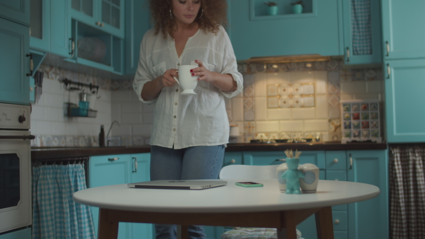 Young curly 20s woman making tea and coming to table with cup. Smiling female opening laptop for working at home on blue kitchen.