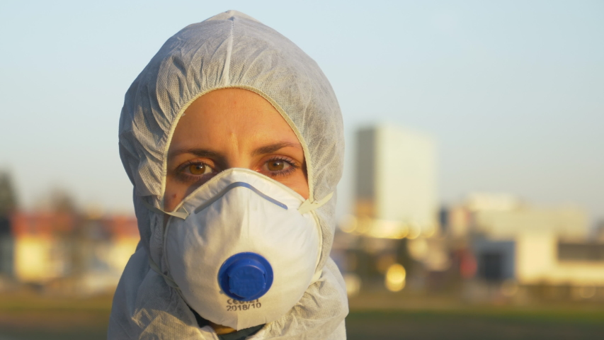 SLOW MOTION, CLOSE UP, PORTRAIT, DOF: Young nurse wearing a protective facemask and suit stands at a coronavirus safety checkpoint on sunny morning. Caucasian nurse during the covid-19 outbreak. Royalty-Free Stock Footage #1048449550