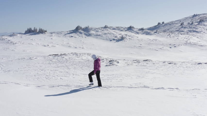 Drone following young woman in mountains walking alone. Beautiful landscape covered with snow high in mountains. White young caucasian model searching for adventures in sunny morning - 4k