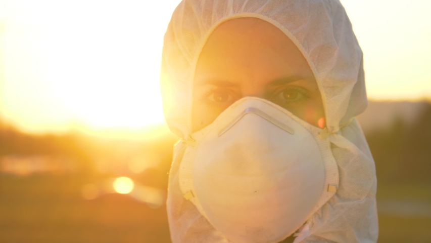 SLOW MOTION, CLOSE UP, LENS FLARE, PORTRAIT, DOF: Female doctor wearing a facemask and suit stands outside in the golden sunset. Nurse wears a protective suit and mask during the COVID19 outbreak | Shutterstock HD Video #1048468894