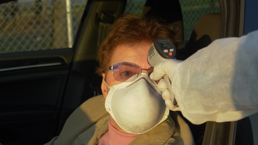 SLOW MOTION, CLOSE UP, DOF: Female driver wearing a facemask gets her temperature measured before entering the city during the covid-19 pandemic. Nurse measuring elderly driver's body temperature. | Shutterstock HD Video #1048468966