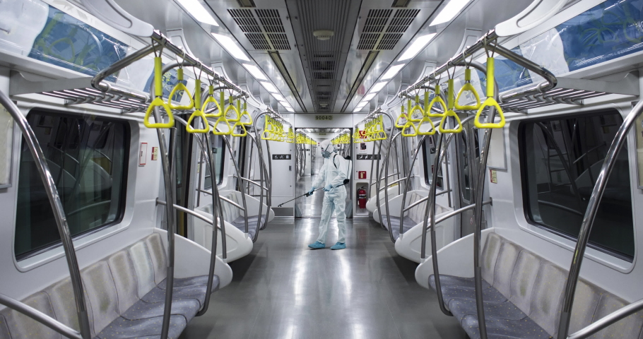 HazMat team in protective suits decontaminating metro car during virus outbreak. 50 FPS Slow motion