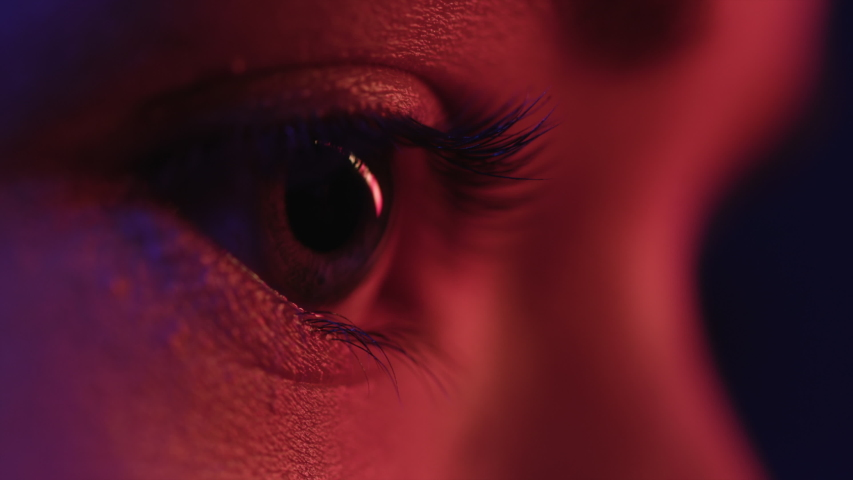 Pretty Eyes of Woman in Colourful Neon. Girl Looking Around at Studio. Abstract Shot of Female Face and Skin with Multi-Colour Flickering of Modern Street Signs. Concept of Young Lady in Red Lighting
