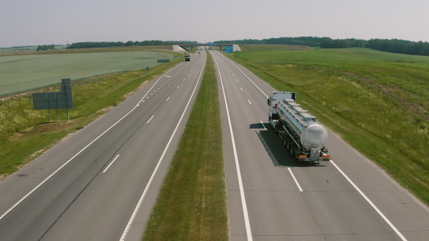 Aerial view. Rear view of giant tank truck or fuel truck drive. Transportation overland delivery of goods and oil. Modern era, pollution concept. Global warming fossil burning problem.   Shutterstock HD Video #1048477408