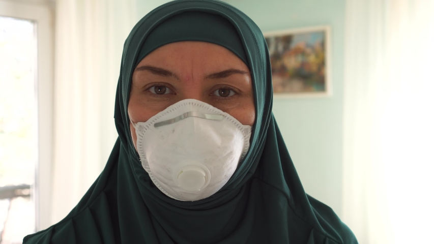 Coronavirus COVID-19 pandemic. Muslim woman in protective medical mask. Muslim Americans Black Lives Matter