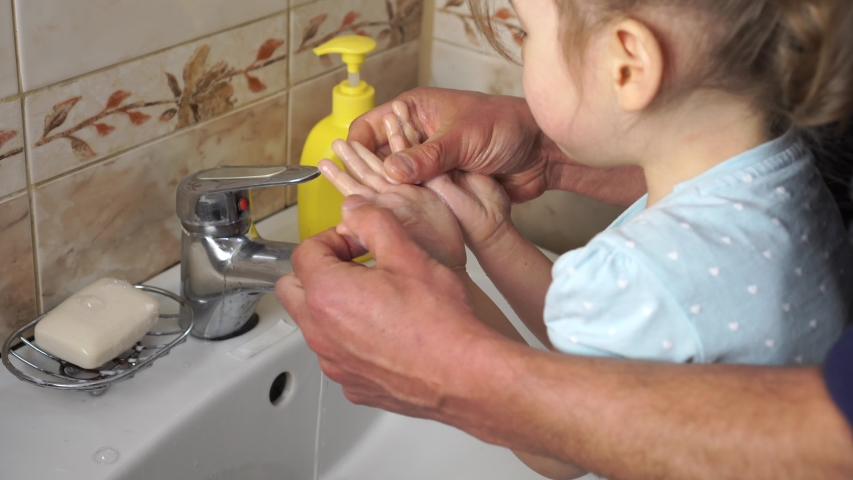 Protection and disinfection against coronavirus (COVID-19). Dad washes a small child's hands with soap over the sink with running water. Personal hygiene
