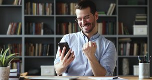Amazed happy businessman receiving sms message reading good news. Excited overjoyed male winner celebrating success looking at smart phone sitting at home office desk. Mobile victory concept
