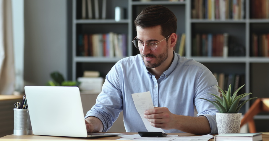 Focused businessman accountant doing calculation for online financial report at workplace. Serious man using calculator paying bill online holding paper sitting at home office desk. Accounting concept